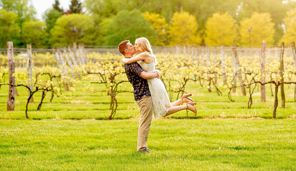 engaged couple kiss and embrace during golden hour at gervasi vineyard