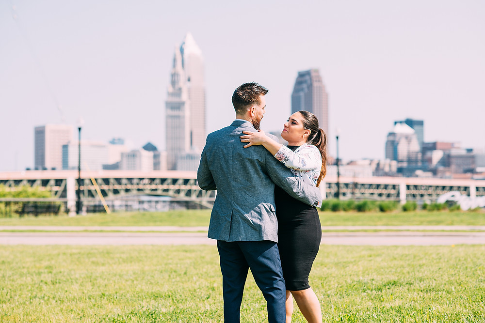 Man and woman slow dance on grass with the Cleveland skyline in the background