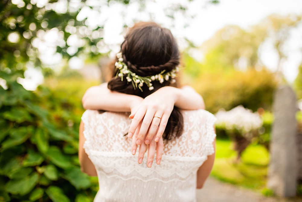 brides embrace at wedding outside by trees