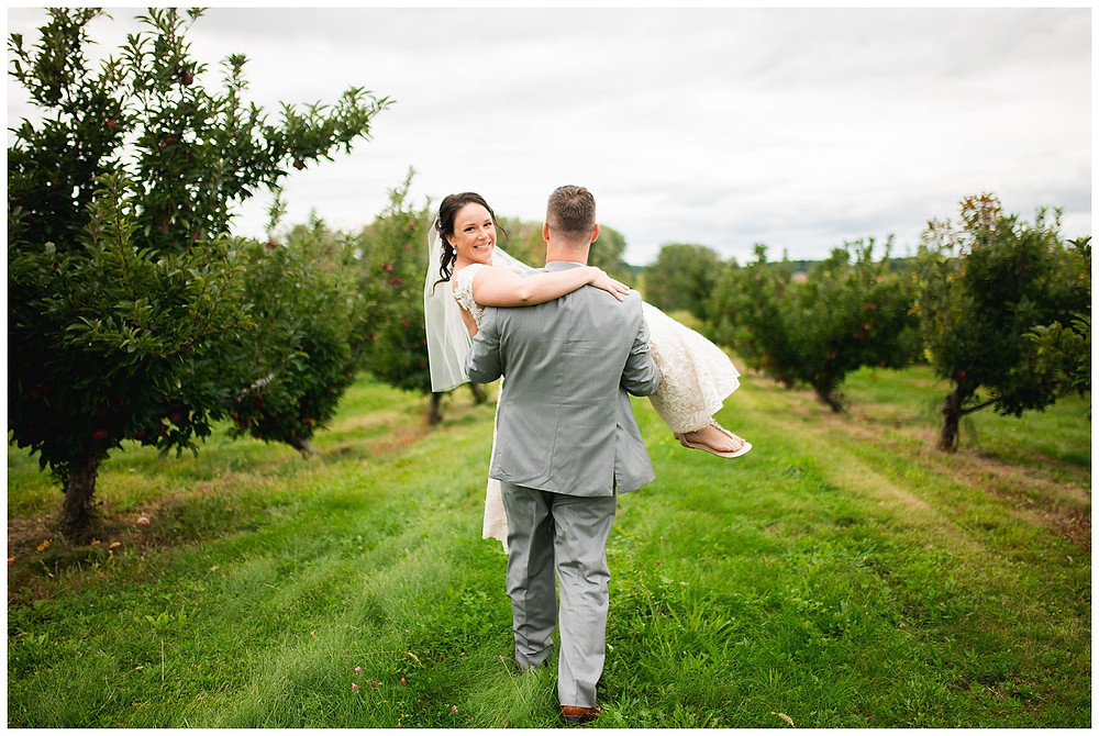 bride is carried away by groom in an apple orchard near cleveland Ohio