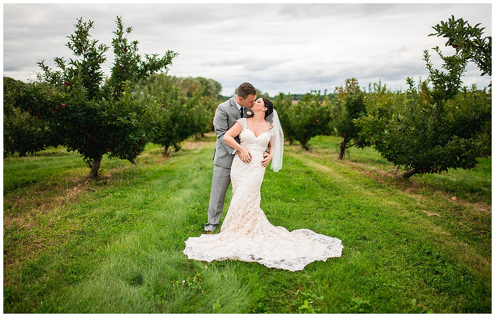 bride and groom kiss on apple orchard during fall wedding at hillcrest fun farm