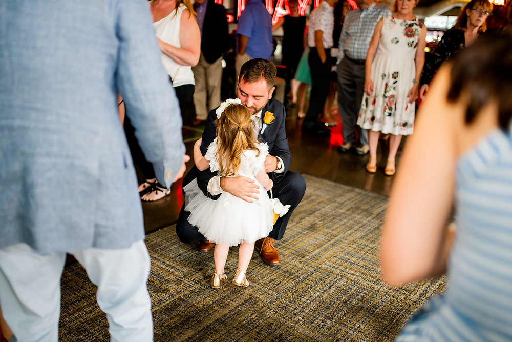 groom hugs flower girl during wedding ceremony in cleveland ohio