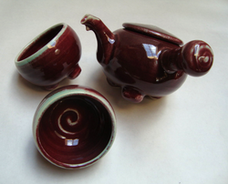 Small, red, side-handled teapot set.