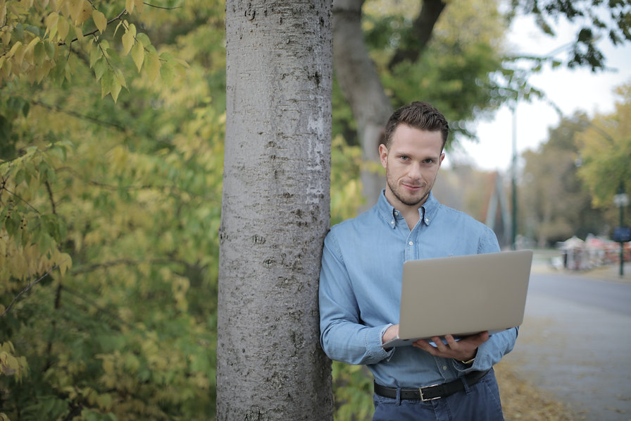 positive-young-man-using-laptop-near-tre