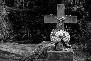 Algures em Trás-os-Montes, junto a um caminho pedestre por entre montes e vales, num lugar absolutamente improvável, no meio do nada, aparecem à nossa esquerda duas sepulturas: crucifixos de granito, ornados com flores cuidadas e de cores vivas. Por detrás, um olheiro — uma espécie de pântano em forma de poça grande. O impacto daquele cenário é arrepiante para quem é apanhado de surpresa. Terão sido, certamente, duas pessoas que ali caíram e não conseguiram sair, tendo ficado lá enterradas. Não sendo possível resgatar os corpos para serem sepultados, aquele local foi transformado em campa improvisada. As cruzes, que materializam e permitem simbolizar aquelas mortes, assim como as vidas que nelas terminaram, tornam-se sustentáculos da elaboração possível desse desencontro traumático.