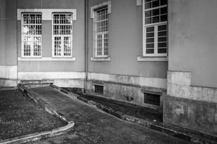 """Em tempos chamei-lhe """"Metáfora de um outro desencontro"""". É uma fotografia das traseiras de um pavilhão do antigo Hospital Júlio de Matos, em Lisboa. Todo o peso simbólico daquela instituição parece condensar-se neste caminho que termina com dois degraus que dão acesso a uma janela gradeada. Ao lado há uma porta, iluminada, mas não é aí que o caminho vai dar. Também poderíamos descrever a imagem em sentido inverso: Num hospital psiquiátrico há uma sala com duas janelas gradeadas. Se porventura não fossem gradeadas e não fossem janelas, mas portas, de uma delas seria possível aceder, descendo dois degraus, a um caminho que passa por entre as árvores do jardim."""
