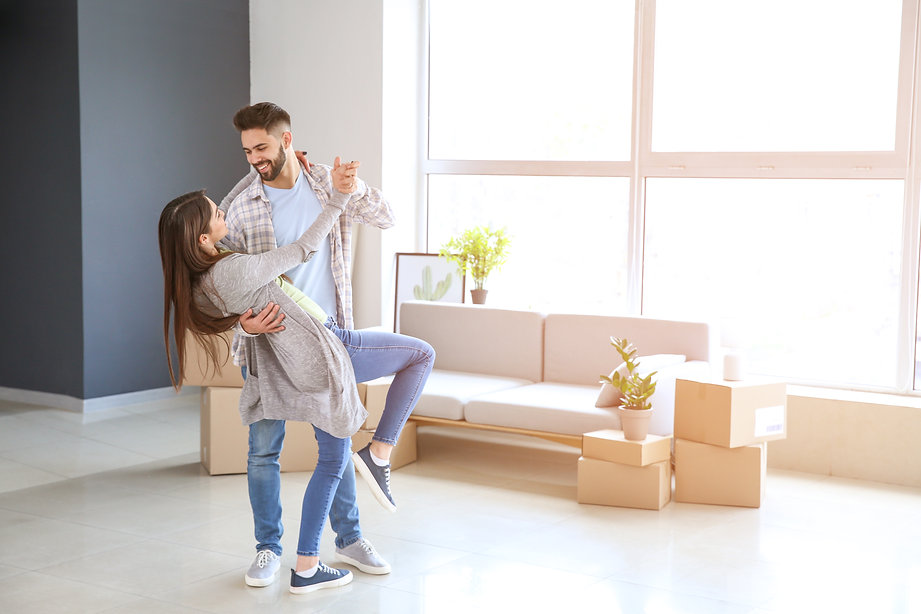 Young couple dancing in their new house.
