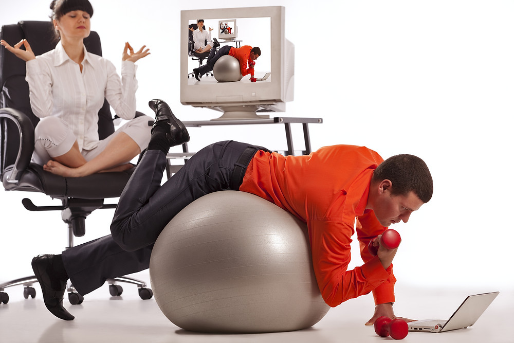 Young businessman doing push-ups with dumbbells, looking on laptop screen. His c