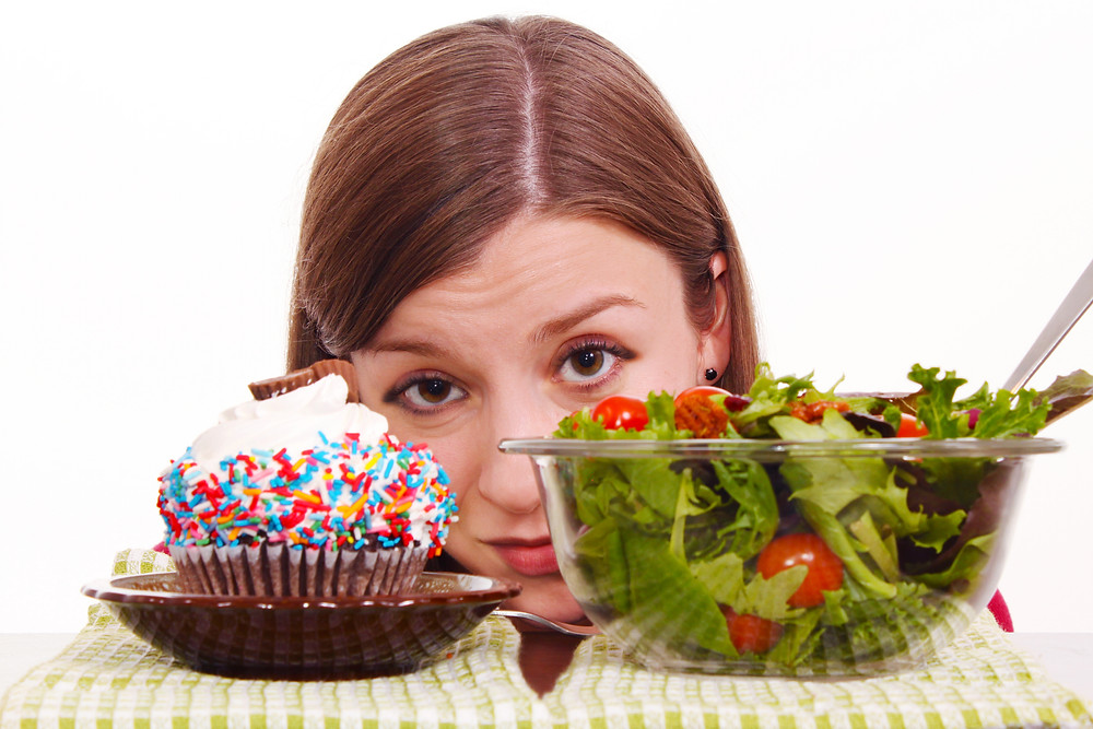 A girl deciding between cake or salad.jpg