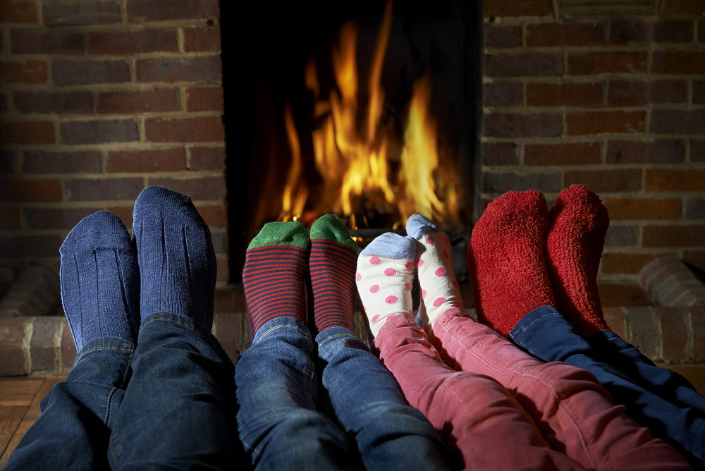 Family Wearing Socks Warming Feet By Fire.jpg