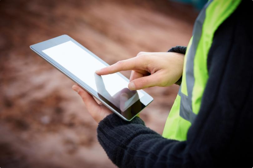 Field service technician in yellow vest on mobile tablet