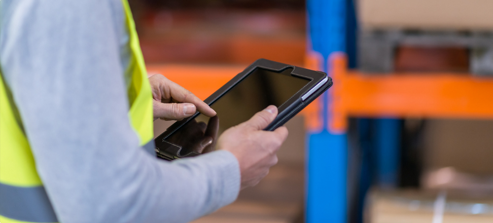 Contractor in yellow vest using mobile tablet at work