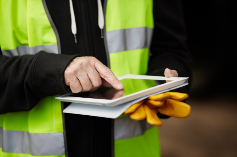 Field service worker in yellow vest holding a mobile tablet