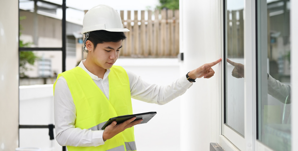 Young field service worker in a yellow vest with a mobile tablet at a clients house