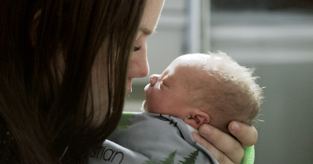 Mother nose to nose with newborn infant.