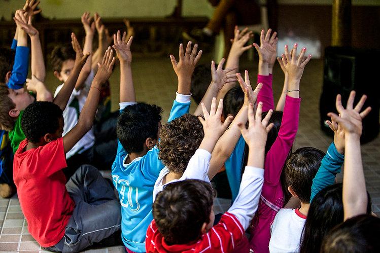 Crianças participando do momento pedagógico. Sentadas no chão elas levantam as mãos em tom de celebração.