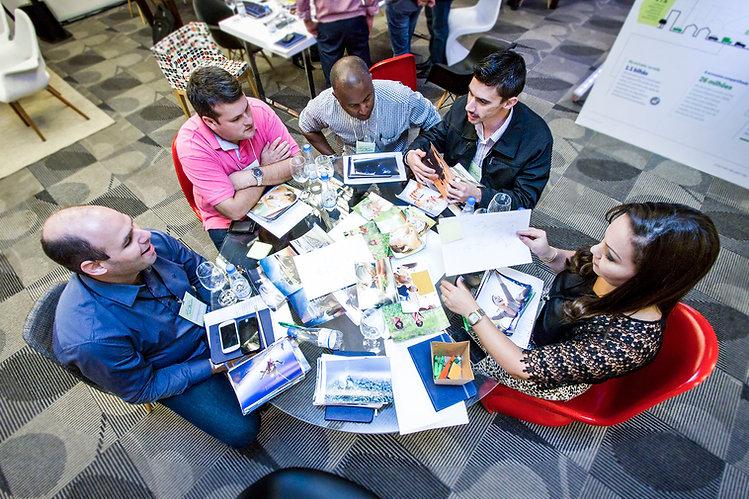 workshop de cocriação com clientes. Pessoas sentadas ao redor da mesa olham fotos e discutem.