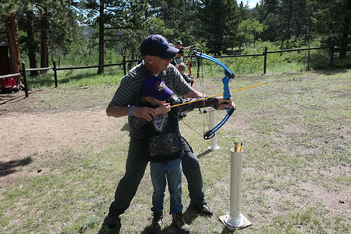 man helps grandson take aim with compound bow.