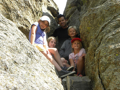 "four kids and one young adult smiling in a narrow rock crevasse called ""Hidden Room"""