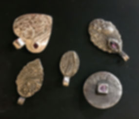 five examples of shaped and designed bronze colored precious metal clay pieces.