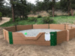 green ball in sand filled gaga ball pit standing about two and a half feet tall.