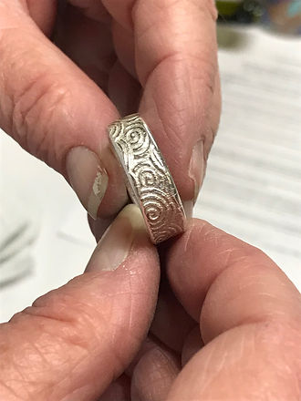 close up of person holding silver colored ring