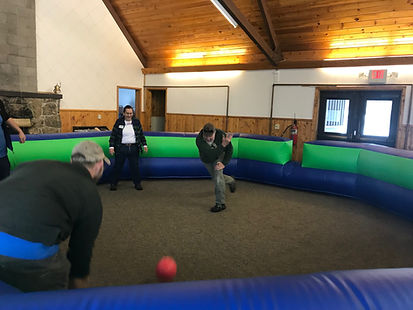 four adults hitting a ball in an indoor inflatable gaga ball pit