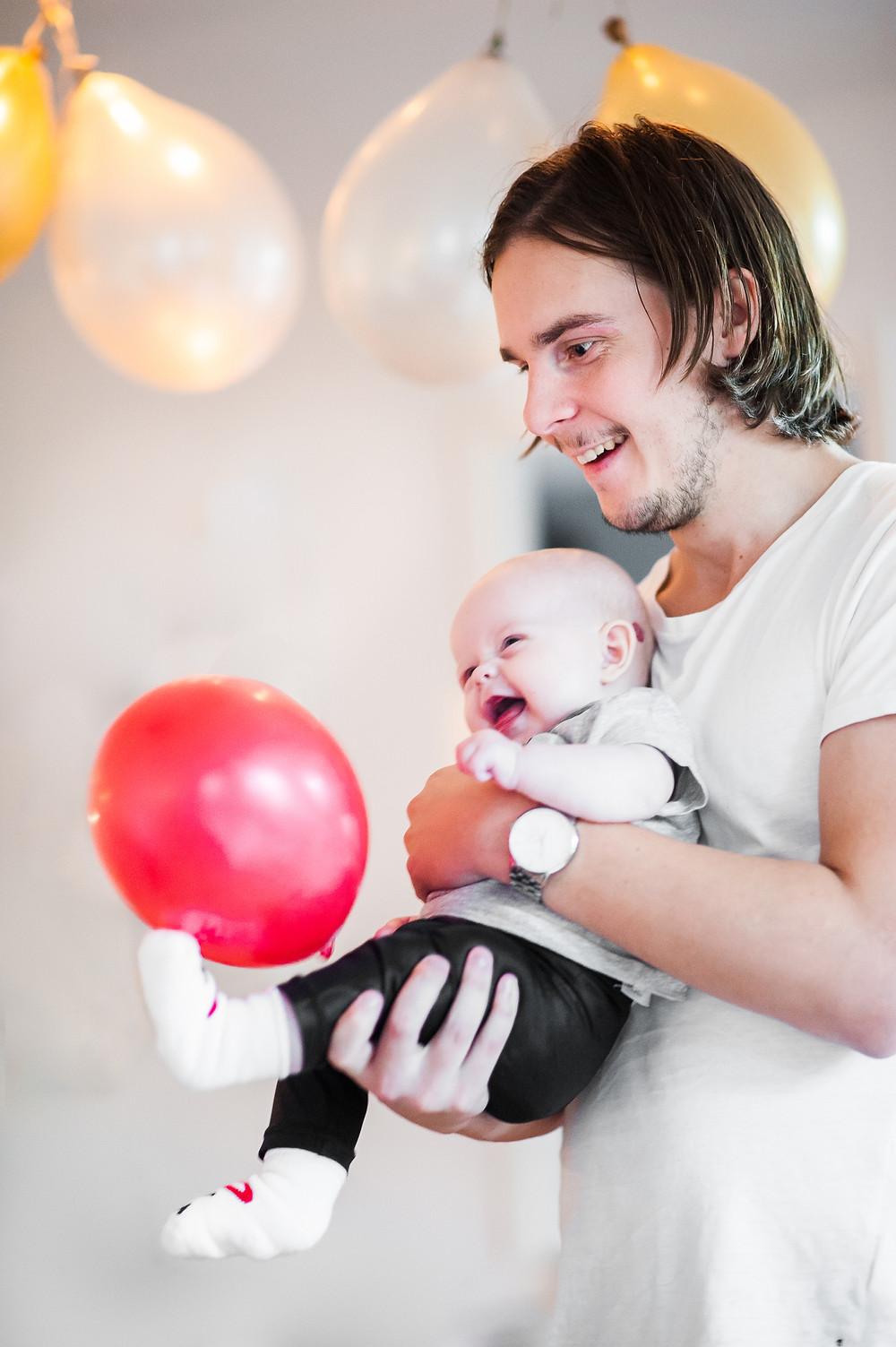Pappa och dotter busar med ballong