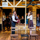 Scott Galbreath as Lloyd and Joan Milburn as Poppy Norton-Taylor surrounded by the cast of Noises Off.