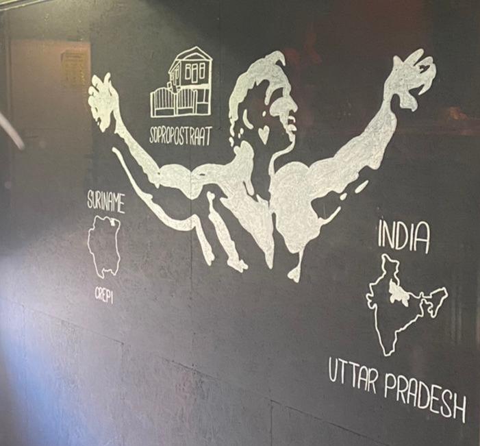 Man met armen wijd, een huis, Suriname en India getekend op een muur