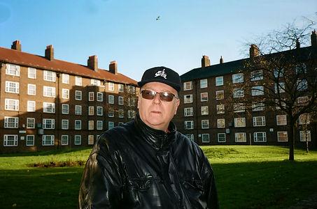 man infront of estate, hat