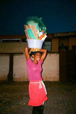 Woman, vendor, basket, head, drinks, purple t shirt, red dress, Accra, Ghana, street vendor