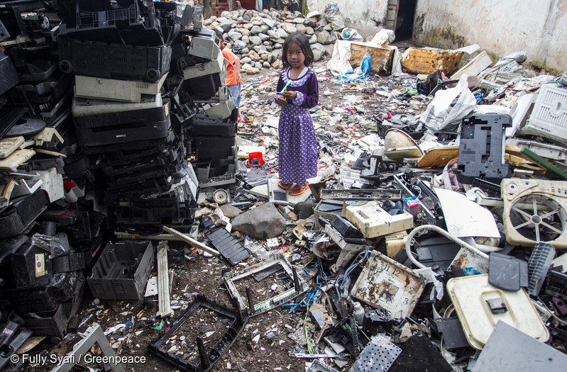Small girl in purple dress standing amidst endless piles of broken and discarded technology.