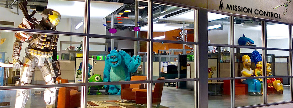View inside the Idea Planet office showing life-size video game characters and theatrical displays for Halo Reach, Monsters, Inc., and The Simpsons.