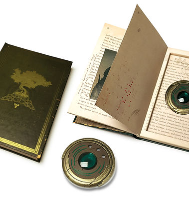 "Book packaging with back cover indention that houses the Strange coin, a 4"" diameter bronzed coin with green gem."