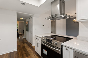 This small kitchen is packed with high-end finishes. From a customized modern hood vent to a drawer microwave. It even boasts two-toned matte black and stainless steel cabinet hardware. And a single basin-sink with drop-in removable cutting board. Including wide-planked laminate flooring!