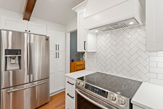A full kitchen remodel boasting modern conveniences while staying true to the classic style of the home. White shaker cabinets, herringbone and subway tile backsplash, with open beam ceiling, charming wet bar and window seating. No detail was overlooked in this stylish kitchen.