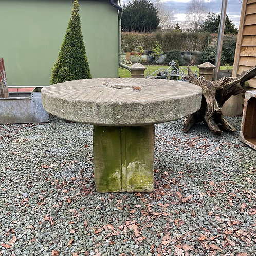Old Millstone mounted on a sandstone block as a garden table