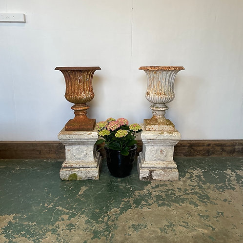 Pair of Victorian Cast Iron Urns mounted on the original terracotta plinths.