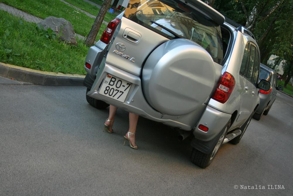 Женщина, что-то ищущая в багажнике джипа