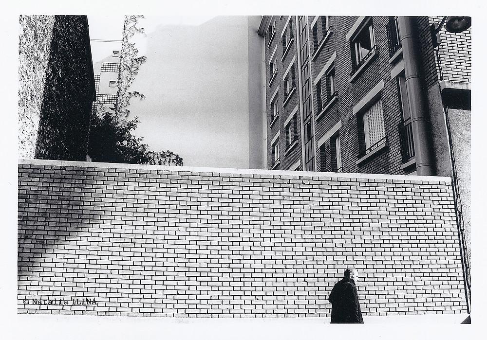 человек, спешащий по своим делам, на фоне кирпичной стены в не туристическом 12 районе