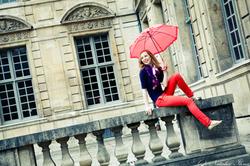 Девушка с зонтиком на каменном забор