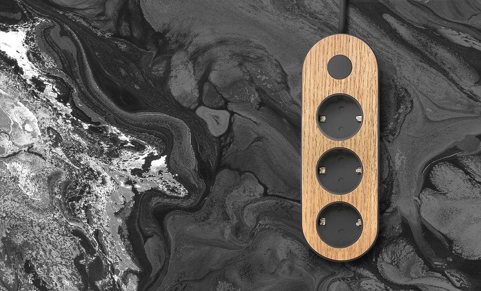 Dark design power strip with oak wooden top on dark background. Nolla strip with Finnish design
