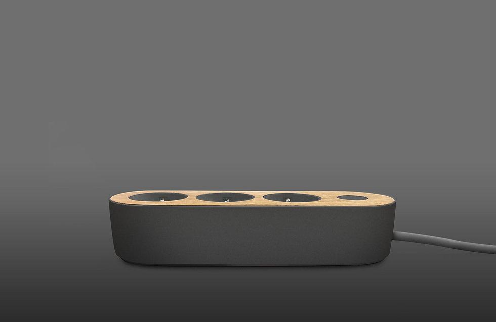 Design power strip with oak wooden top on dark background side view Nolla strip Finnish design
