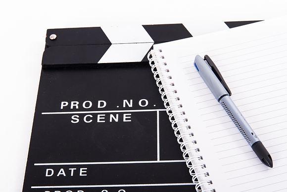 Black cinema clapper board and notebook