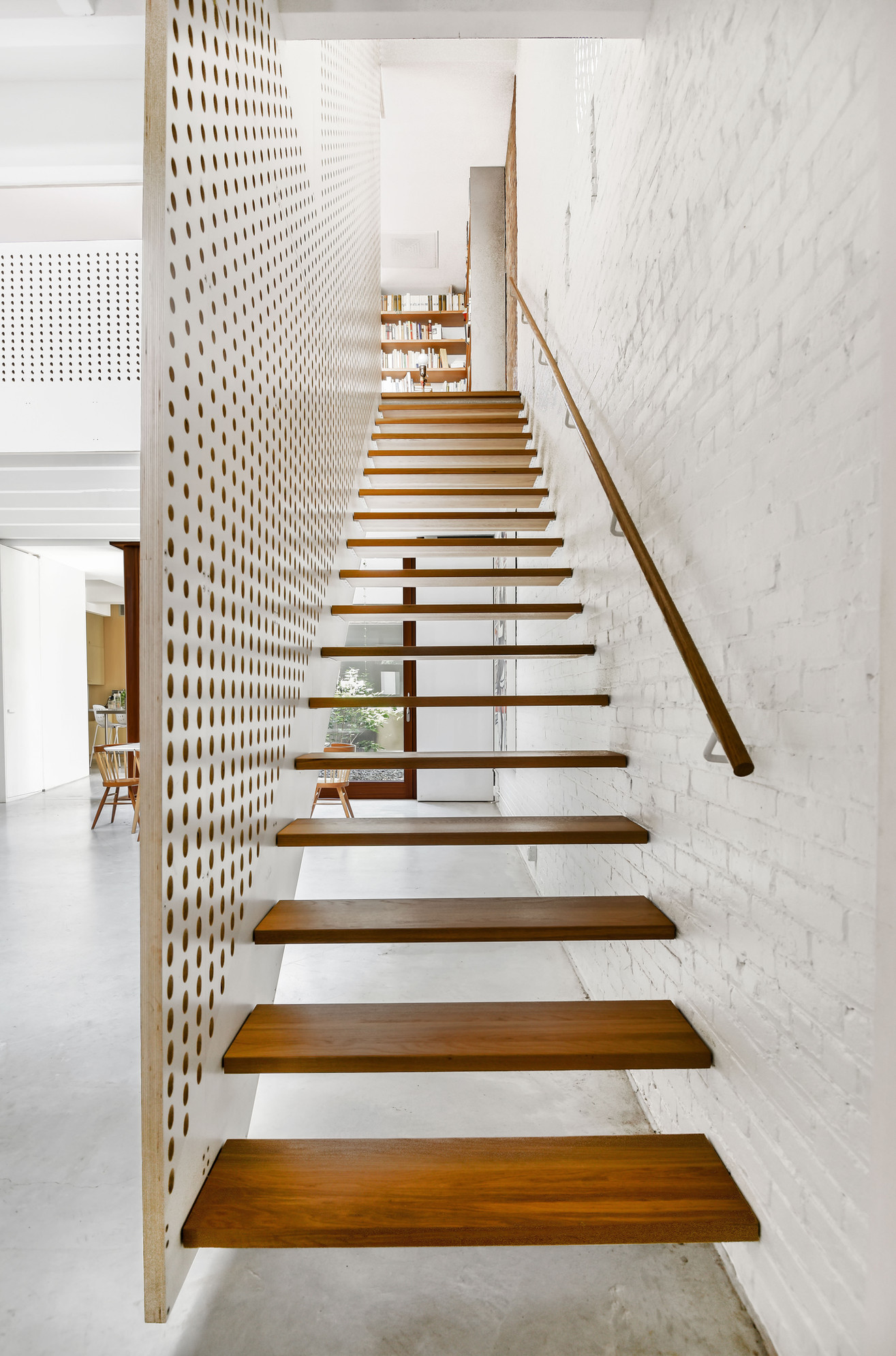 The stair wall is made of perforated plywood. Angle of holes radiates with 15 deg change.