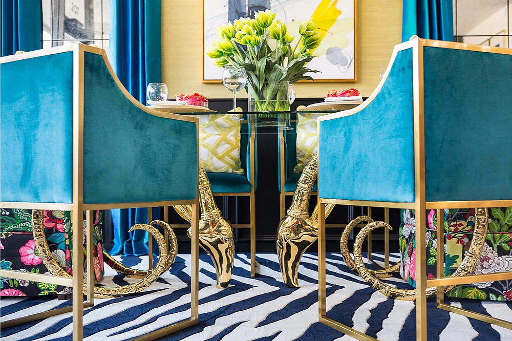 Blue zebra pattern rug with a glass table that has golden antelope legs. Accented with colourful Chinoiserie fabric. Image: veronicasolomon.com
