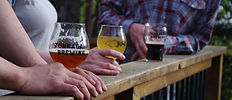 People holding glasses of Turnagain Brewing Beers resting on a rail