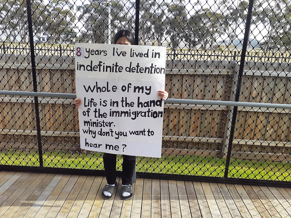 Woman stands in front of high fence, holding a sign that reads, '8 year I've lived in indefinite detention. Whole of my life is in the hands of the immigration minister. Why don't you want to hear me?'