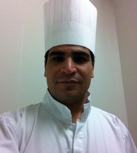 Man wearing tall chef's hat and chef's white uniform.